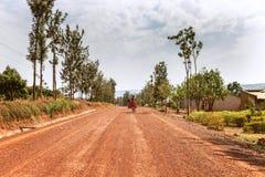 KIBUYE, RWANDA, ÁFRICA - 11 DE SEPTIEMBRE DE 2015: Hombre desconocido El hombre que completa un ciclo en la tierra africana roja Fotos de archivo