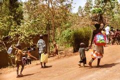 KIBUYE, RWANDA, AFRÄ°CA - 11 DE SEPTIEMBRE DE 2015: Mujer y niños no identificados El plátano que lleva de la mujer africana en s Fotografía de archivo libre de regalías