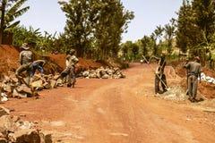 KIBUYE, RWANDA, AFRÄ°CA - 11 DE SEPTIEMBRE DE 2015: Trabajadores no identificados Los trabajadores que trabajan debajo del sol Imágenes de archivo libres de regalías