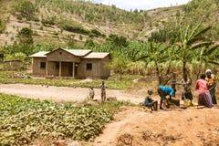 KIBUYE RWANDA, AFRÄ°CA - SEPTEMBER 11, 2015: Oidentifierade kvinnor De afrikanska kvinnorna och deras barn runt om springbrunnen  Arkivbild