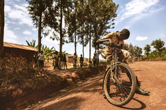 KIBUYE, RWANDA, AFRİCA - SEPTEMBER 11, 2015: Unidentified young boy. The African young boy on dirt road with his bicycle. Stock Images