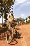 KIBUYE, RWANDA, AFRİCA - SEPTEMBER 11, 2015: Unidentified young boy.  A young man on bike. Stock Photos