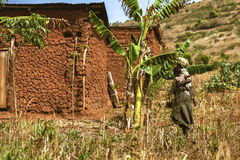 KIBUYE, RWANDA, AFRICA - SEPTEMBER 11, 2015: Unknown woman and baby. The woman walking to her house that is built by mud and earth near the banana field. She Royalty Free Stock Photos
