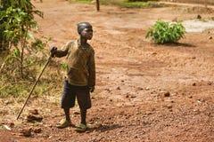 KIBUYE, RWANDA, AFRIKA - SEPTEMBER 11, 2015: Onbekend kind De kleine jongen bevindt zich in aardeweg met zijn oude en gescheurde  Stock Afbeelding