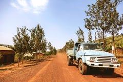 KIBUYE, RWANDA, AFRIKA - SEPTEMBER 11, 2015: Onbekende arbeiders De lichtblauwe oude vrachtwagen die de arbeiders op de omringde  Stock Foto