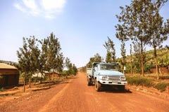 KIBUYE, RWANDA, AFRIKA - SEPTEMBER 11, 2015: Onbekende arbeiders De oude vrachtwagen die de arbeiders op de rode aardeweg vervoer Royalty-vrije Stock Afbeelding