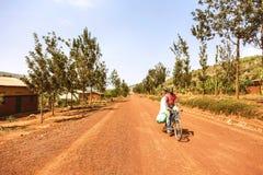 KIBUYE, RWANDA, AFRIKA - SEPTEMBER 11, 2015: Onbekende mensen dragende materialen met fiets op de duidelijke rode aardeweg zonder Royalty-vrije Stock Fotografie