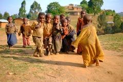 Kibuye/Rwanda - 08/25/2016: Groep Afrikaanse pygmy stamkinderen die en pret in etnisch dorp glimlachen hebben royalty-vrije stock afbeelding