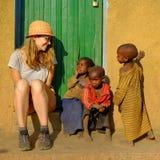 Kibuye/Rwanda - 08/25/2016: Toerist met een groep Afrikaanse pygmy stamkinderen die en pret in etnisch dorp glimlachen hebben royalty-vrije stock afbeeldingen