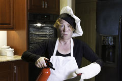 Kichen disaster in apron with fire extinguisher and pan Royalty Free Stock Photos