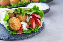 Kichererbse Falafelbälle mit Gemüse und Soße, Rollensandwichvorbereitung lizenzfreie stockfotos