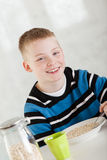 Kicherndes blondes Kind, das Hafermehl in der Schüssel isst Stockbilder