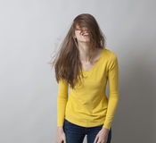 Kicherndes Mädchen 20s, das oben zum Spaß ihr Haar verwirrt Lizenzfreie Stockfotos