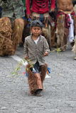 Kichwa boy wearing chaps walking on the street during inti raymi. Julne 29, 2017 Cotacachi, Ecuador: kichwa boy wearing chaps walking on the street during inti Royalty Free Stock Images