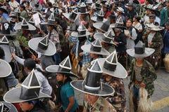 Kichwa män som bär extra stora sombrero som dansar på gatan Arkivfoto