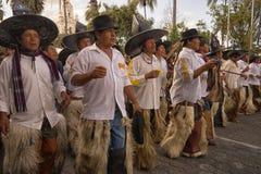 Kichwa men wearing chaps. June 29, 2017 Cotacachi, Ecuador: men walk the parade wearing extra large hats and chaps during Inti Raymi celebration royalty free stock photo