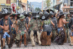 Kichwa men wearing chaps performing ritual dance on the street d. June 29, 2017 Cotacachi, Ecuador: kichwa indigenous people with extra large hats and chaps royalty free stock images