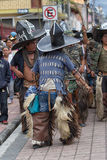 Kichwa men wearing chaps performing ritual dance on the street d. June 29, 2017 Cotacachi, Ecuador: kichwa indigenous people with extra large hats and chaps royalty free stock photo