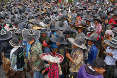 Kichwa men wearing extra large sombreros dancing on the street. June 29, 2017 Cotacachi, Ecuador: indigenous Kichwa crowd on the street celebrating Inti Raymi royalty free stock image