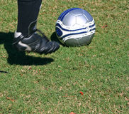 Kick it!. Boy's foot in motion kicking soccer ball royalty free stock photo