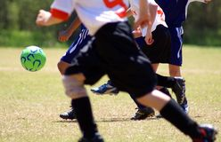 Kick the ball. Several boys playing soccer going for a green ball stock images