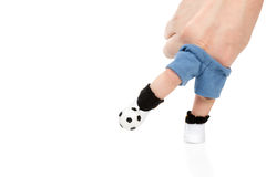 Kick a ball. Two fingers, dressed in sports clothes hit the ball simulating a football player isolated on white background Stock Image