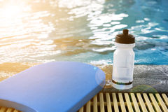 Kick board and water bottle on swimming pool Stock Photos