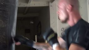 Kick boxer boxing as exercise for the big fight. Boxer hits punching bag. Young boxer trains on punching bag stock footage