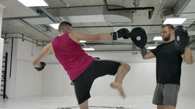 Kick boxer fulfills with the trainer the slopes of the udra and the dives on the paws in slow motion.  stock video