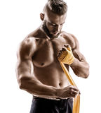 Kick-boxer preparing his fists for a fight. Photo of athletic man applying yellow boxing bandages isolated on white background. Strength and motivation royalty free stock images
