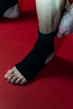 Kick Boxer Putting Straps On His Foot Royalty Free Stock Images