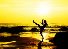 Kick boxing young woman on the beach. Young woman doing kick boxing move working out on the beach at golden sunset Stock Images
