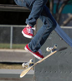 Kick Flip Skateboard. Skateboarder doing a trick on a skateboard with red shoes royalty free stock photo