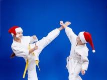 Kick leg and block are training kids in karategi Stock Images