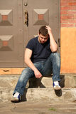 Kick out of home. A young man sits on the stairs near the house Royalty Free Stock Photography