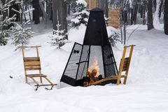 Kick sleds around Roaring Bonfire in Winter. Flames from a campfire are contained in a sturdy outdoor fireplace in a winter wonderland in Ontario cottage country Royalty Free Stock Photography