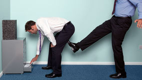 A kick up the backside. Photo of a businessman bending over to get something out of a drawer as a colleague kicks him up the backside Royalty Free Stock Images