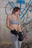 Kickbox fighter getting ready. Young woman getting ready for box fight in industrial place Royalty Free Stock Photography