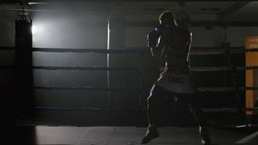 Kickbox fighter shadow boxing in the ring. The athlete fights with his shadow. Young boxer in training throwing a punch. With bandages on his fists as he works stock video footage
