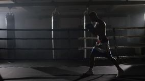 Kickbox fighter shadow boxing in the ring. The athlete fights with his shadow. Young boxer in training throwing a punch. With bandages on his fists as he works stock footage