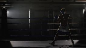 Kickbox fighter shadow boxing in the ring. The athlete fights with his shadow. Young boxer in training throwing a punch. With bandages on his fists as he works stock video