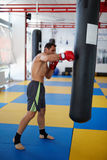 Kickbox fighter training with the punch bag Stock Photos