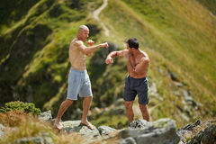Kickbox fighters sparring in the mountains Royalty Free Stock Photo