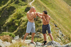 Kickbox fighters sparring in the mountains Stock Photos