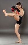 Kickbox flicka som levererar en spark Arkivbilder