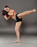 Kickbox girl delivering a kick. Kickbox young woman delivering a kick, over gray background Stock Images