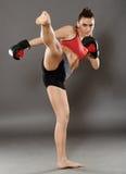 Kickbox girl delivering a kick Royalty Free Stock Photos