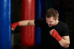 Kickboxer猛击的沙子袋子 免版税库存图片