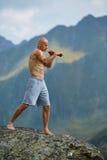 Kickboxer или muay тайская тренировка бойца на скале горы Стоковое Изображение