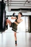 Kickboxer coraggioso che mostra posizione di alta scossa all'interno Fotografia Stock